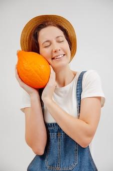 収穫の小さな熟したカボチャの概念を握りしめながら若い女性の農業農家は微笑む