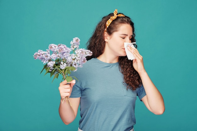 Young female allergic to blooming lilac blowing nose into paper handkerchief while standing over blue wall in isolation