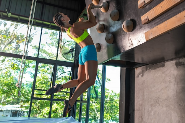 Young female alpinist practicing indoor the rock-climbing on artificial boulder with the safety belts
