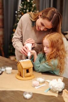테이블에 서있는 동안 휘핑 크림으로 만든 진저 브레드 하우스를 장식하는 젊은 여성과 그녀의 귀여운 딸