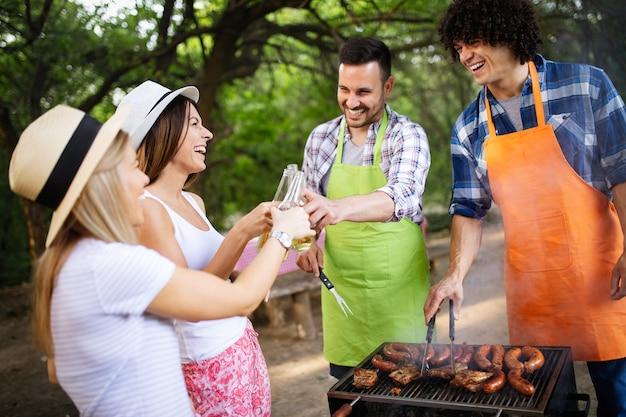 Молодая пара женского и мужского пола, выпекающая барбекю на природе с друзьями