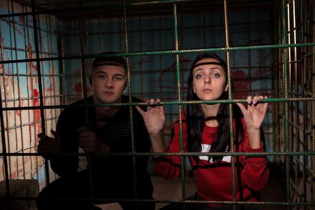 Молодые жертвы женского и мужского пола заключены в металлическую клетку с забрызганной кровью стеной позади них и держат решетку
