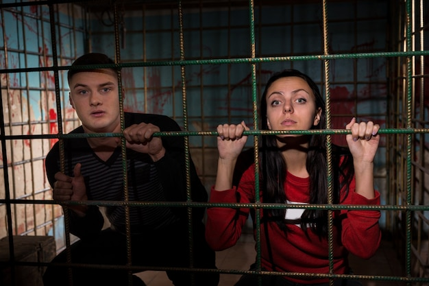 Молодые жертвы женского и мужского пола, заключенные в металлическую клетку с забрызганной кровью стеной позади них, сидят в ужасе в ожидании судьбы