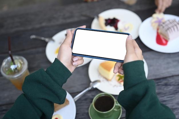 甘いデザートの写真を撮るスマートフォンを持っている若い女性ands。