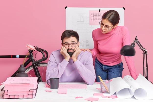 若い女性建築家と男性エンジニアが共同でプロジェクトを進めています。青写真に取り組むのにうんざりしている同僚と一緒にクリエイティブなオフィスでポーズをとる悲しい退屈なひげを生やした男。チームワークの概念