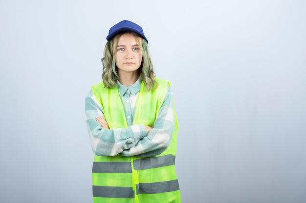 制服を着た若い女性建築家が白い壁を越えた。高品質の写真
