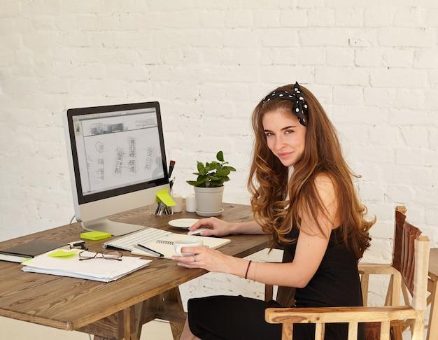 젊은 여성 건축가보고 하 고 사무실에서 작업하는 동안 웃 고. 사무실에서 책상에 앉아 계획 새 사무실 건물을 공부하는 매력적인 젊은 여자