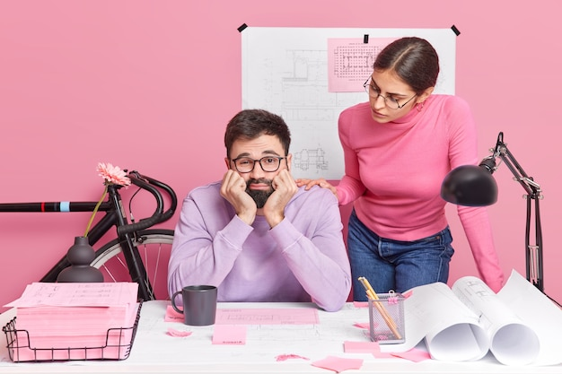Young female architect and male engineer collaborate together for common project. sad bored bearded man poses in creative office with colleague tired of working on blueprints. teamwork concept