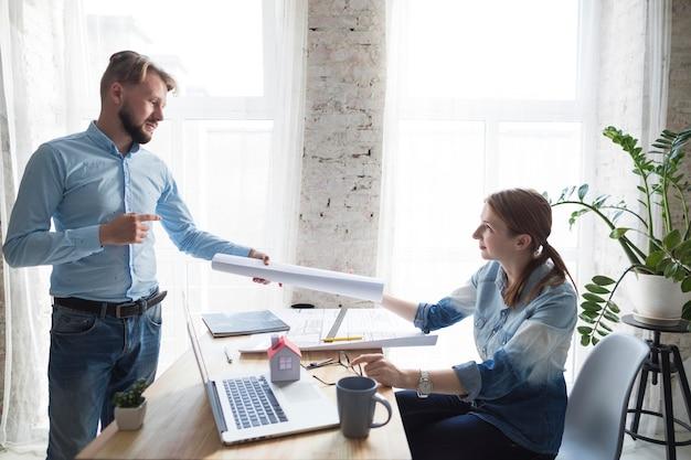 Молодая женщина архитектура, давая план ее коллегам в офисе