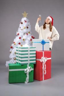 Giovane donna intorno a regali di natale su grigio