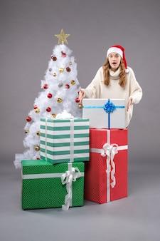 Giovane femmina intorno a regali di natale su grigio