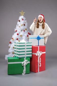Giovane donna intorno a regali di natale sulla luce