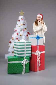 크리스마스 주위에 젊은 여성 회색 바닥 새 해 크리스마스 휴일에 선물