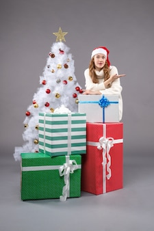 크리스마스 주위에 젊은 여성 회색 바닥에 크리스마스 선물 휴일 선물