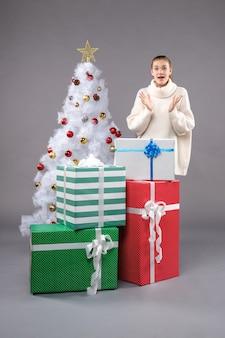 크리스마스 주위 젊은 여성 회색 바닥에 선물