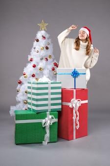 크리스마스 주위 젊은 여성 회색에 선물