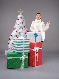 クリスマスの周りの若い女性は灰色のプレゼント