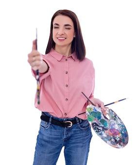 白い背景で隔離の彼女のブラシでプロポーションを測定する若い女性アーティスト