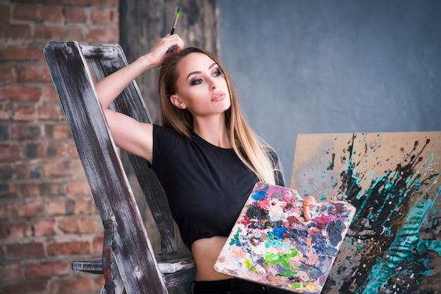 スタジオで抽象的な絵を描く若い女性アーティスト、美しいセクシーな女性の肖像画