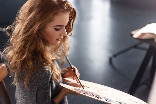 Young female artist painting picture in studio