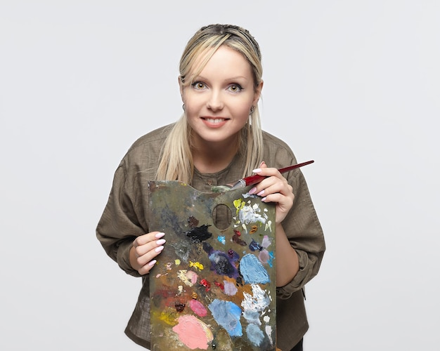 Young female artist poses with a palette and brush in a studio on a white background
