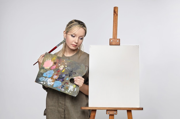 Young female artist stands in front of an empty canvas wondering what to draw