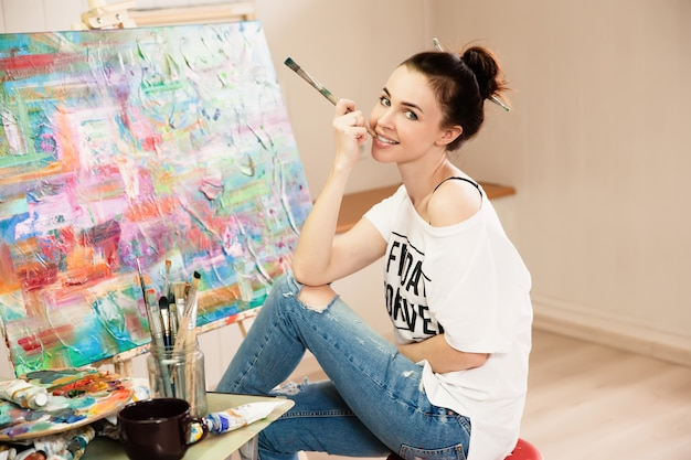 Young female artist working on painting in studio