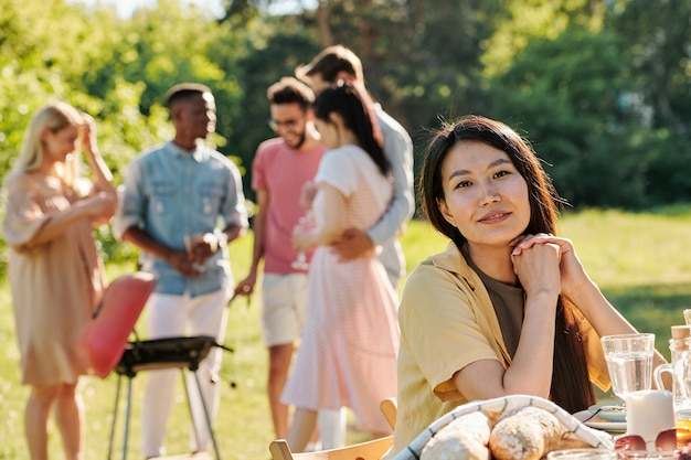 Young female of asian ethnicity sitting by served table on of her intercultural friends making barbecue