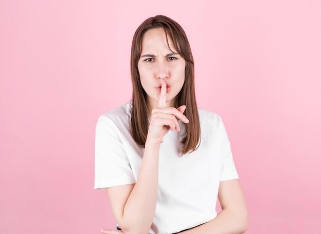 Молодая самка просит молчать с пальцем на губах. молчание и секретная концепция на розовом фоне,