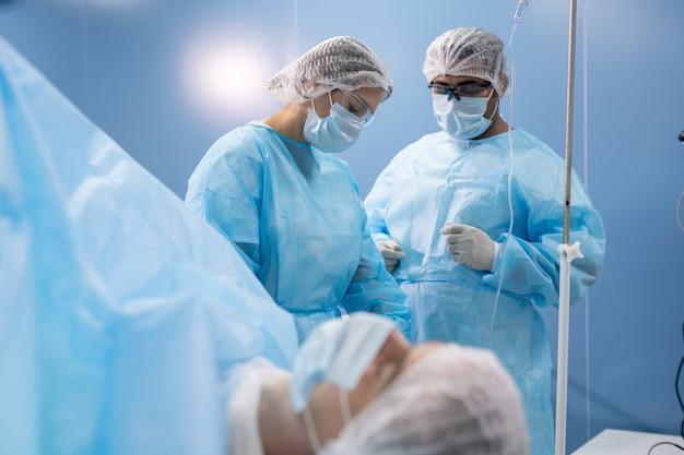 男性外科医と患者の間で手術前に医療機器を準備する保護作業服の若い女性アシスタント