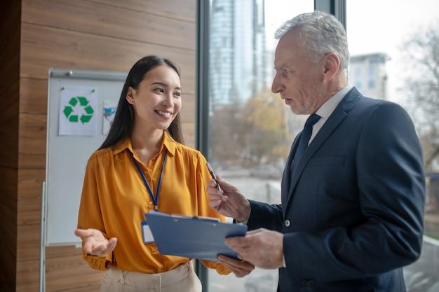 Молодая женщина-помощник улыбается своему седовласому боссу во время разговора