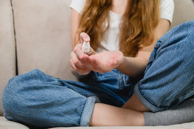 세계 전염병 검역 기간 동안 회색 소파에 있는 젊은 여성은 손, 격리 기간 및 위생 개념에 방부제 스프레이를 바릅니다.