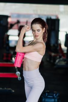 水のボトルを保持しているジムのトレーナーの若い女性