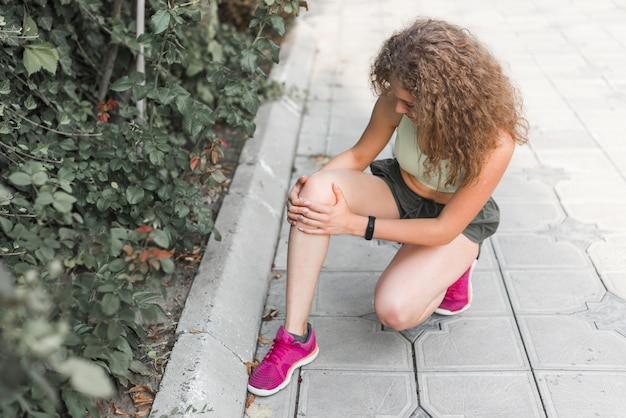 Young female athlete crouching on pavement having knee pain
