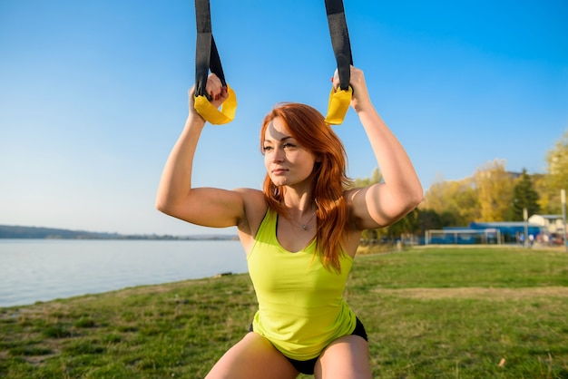 公園でtrxフィットネスストラップを使って朝のエクササイズトレーニングをしている若い女性アスリート。健康的なトレーニングとライフスタイルの概念