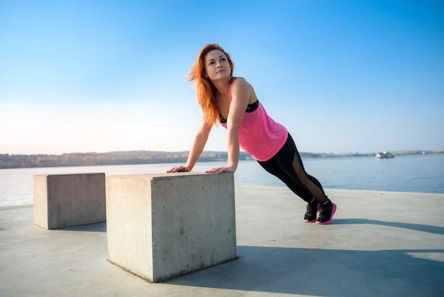 昼間に湖の近くで屋外で腕立て伏せをしている若い女性アスリート