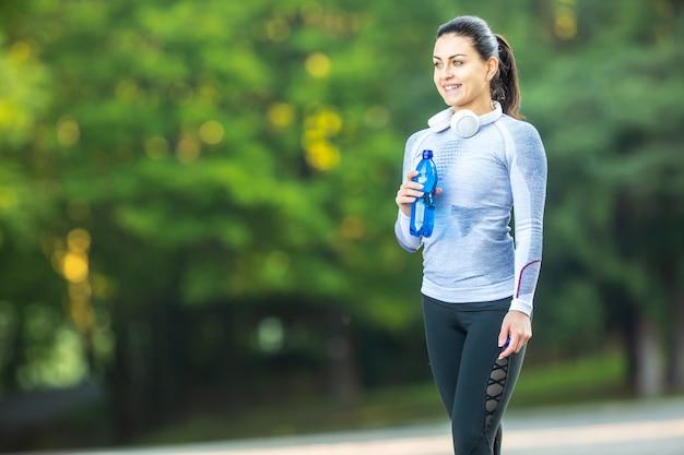 젊은 여성 운동선수는 훈련 후 물을 마신다.
