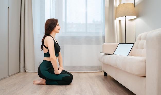若い女性アスリートは、ラップトップでフィットネスのレッスンを勉強しているリビングルームで自宅に座っています