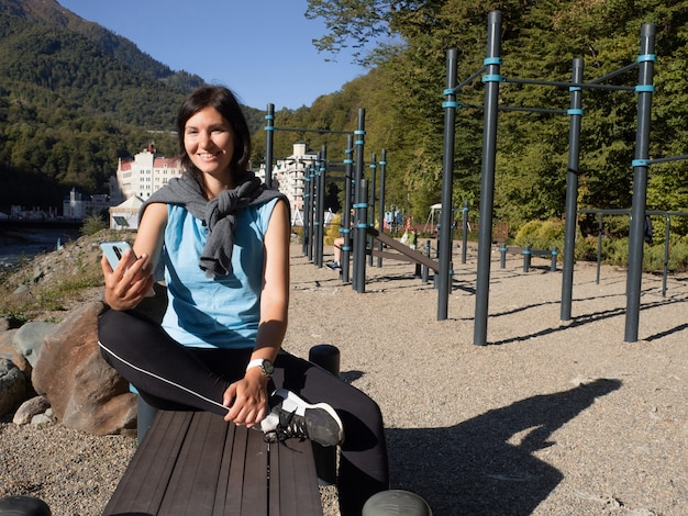 A young female athlete is sitting on an outdoor sports field, resting after training. the happy brunette uses a smart watch and smartphone apps to track sports statistics. outdoor sports activities.