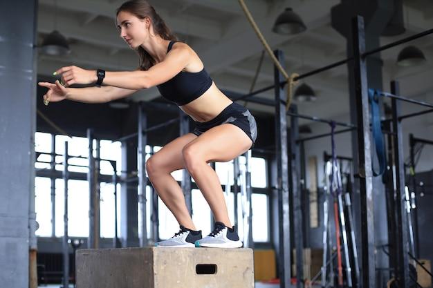 Молодая спортсменка прыгает на коробке в тренажерном зале crossfit.