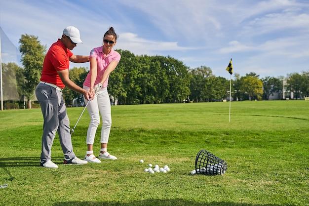 숙련 된 강사의 도움을 받아 코스에서 골프 스윙을 연습하는 젊은 여성 운동 선수