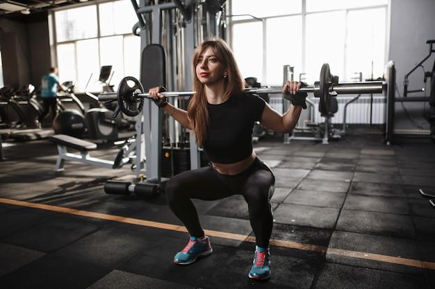 Молодая спортсменка на корточках со штангой в тренажерном зале