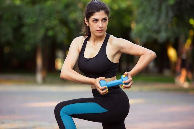 若い女性アスリートが夏の日差しの中で街でトレーニング。美しい女性の練習、ワークアウト。スポーツ、健康的なライフスタイル、運動、活動の概念。ストレッチ、腹筋、abs。