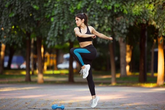 Тренировка молодой спортсменки на улице города в солнечности лета. красивая женщина, практикующих, разработка. концепция спорта, здорового образа жизни, движения, деятельности. растяжка, приседания, abs.