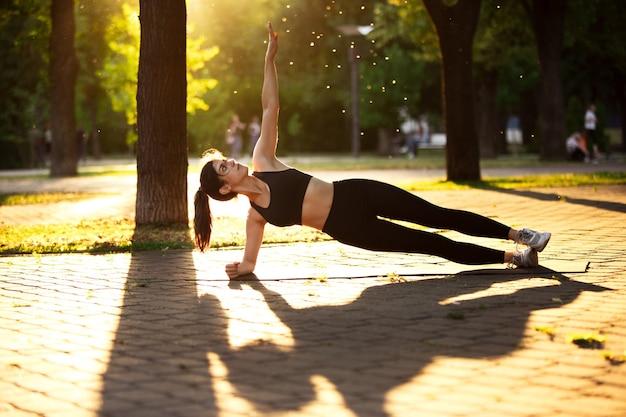 夏の日差しの中で街の通りでトレーニングする若い女性アスリート。練習、ワークアウトの美しい女性。スポーツ、健康的なライフスタイル、動き、活動の概念。ストレッチ、腹筋、abs。