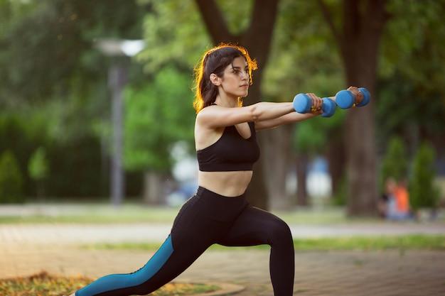 夏の日差しの中で街の通りでトレーニングする若い女性アスリート。