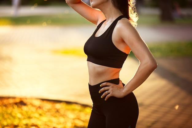 夏の日差しの中で街の通りでトレーニング若い女性アスリート