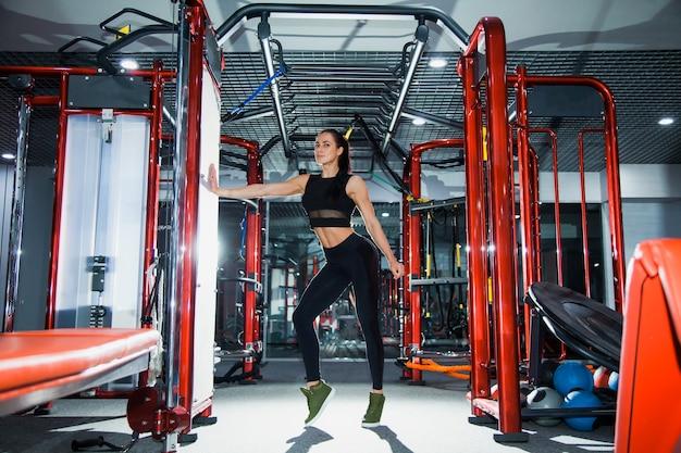맞는 완벽 한 몸을 가진 젊은 여성 운동 선수는 물으로 현대 체육관 보류 셰이 커에서 포즈. 활동적인 라이프 스타일 개념. 스포츠 클럽에서 피트니스 비키니