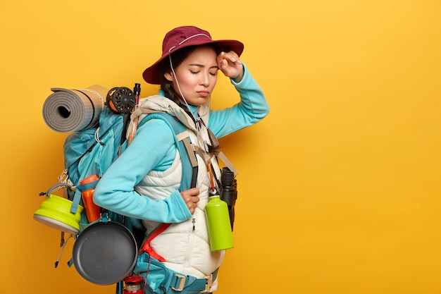Young female backpacker has tired face expression, keeps hand on forehead, feels fatigue after long trip on foot