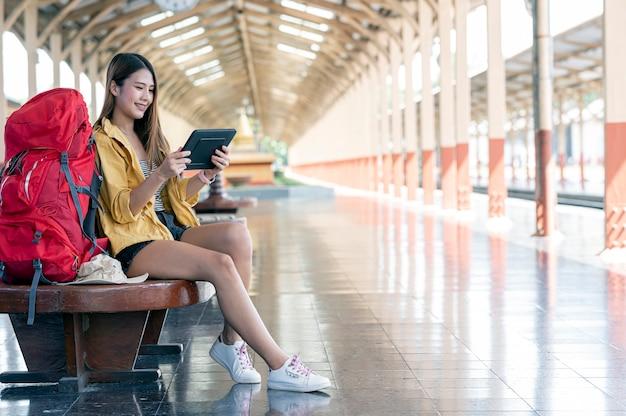 Молодая женщина-туристка с помощью планшета ищет место назначения, сидя на железнодорожной станции